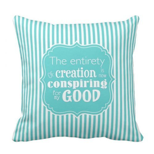"I Am Abundantly Supplied Affirmation Throw Pillow. White typography on an aqua frame features the affirmation ""The entirety of creation is now conspiring for my good,"" all against an aqua and white-striped background."