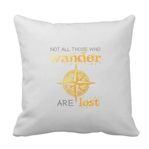 "Inspirational quote throw pillow includes the quote ""Not all those who wander are lost"" in gold and gray typography. Design includes a gold-colored rose compass."